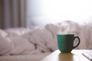 green coffee cup on a nightstand next to a blanket