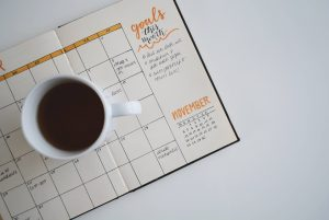 coffee mug sitting on top of a planner notebook