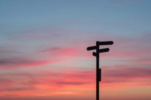 shadow of directional signs against the sky at dusk