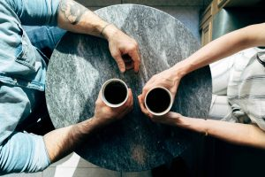 aerial view of two people holding coffee cups on a round table