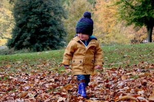 child walking on leaves in daytime